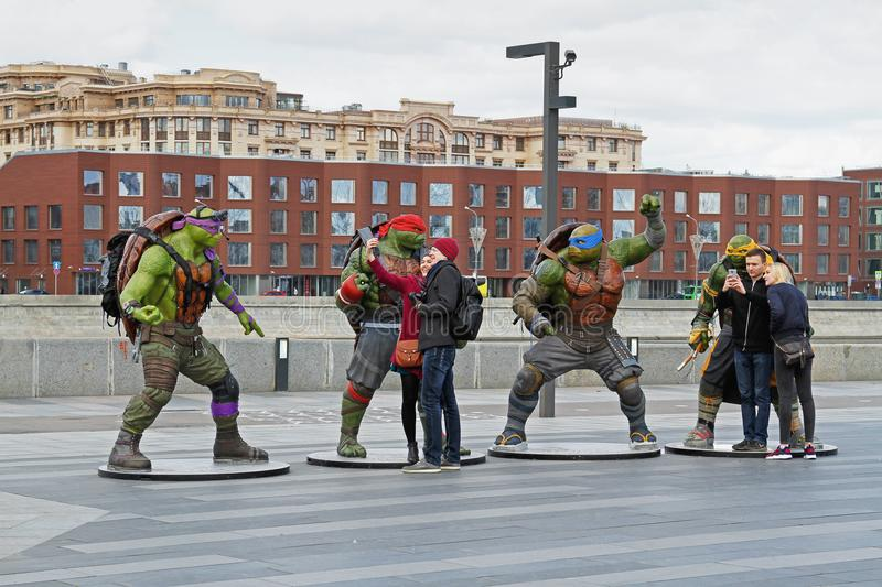 People take a selfie with phone on a background of teenage mutant ninja turtles figures in the park Muzeon in Moscow stock image