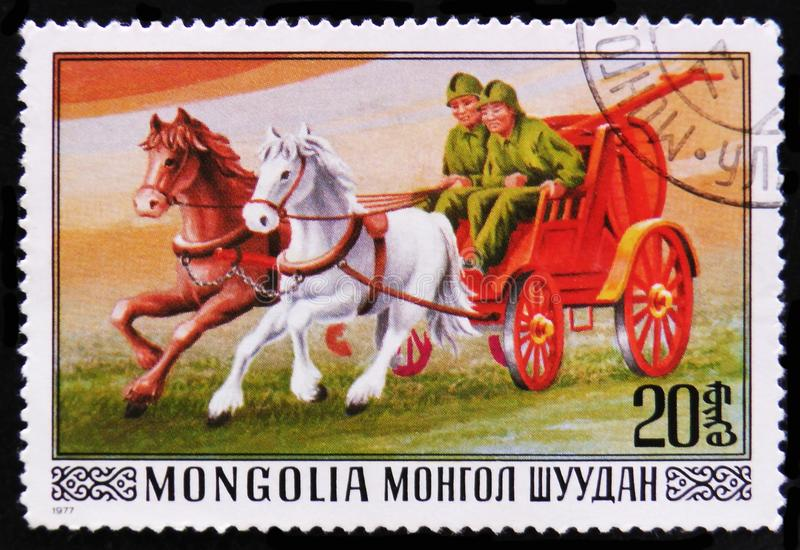 Firefighting carriage and horses, circa 1977. MOSCOW, RUSSIA - APRIL 2, 2017: A post stamp printed in Mongolia shows firefighting carriage and horses, circa 1977 stock image