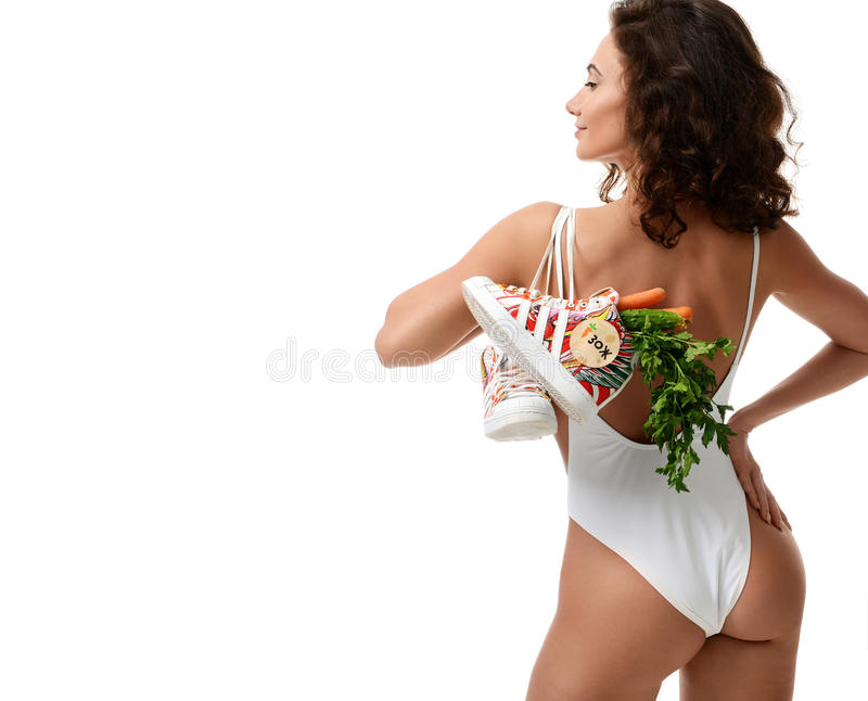 Moscow, Russia - April 12, 2017: Sport woman with adidas superstar shoes full of vegetables on white. Healthy eating concept show royalty free stock image