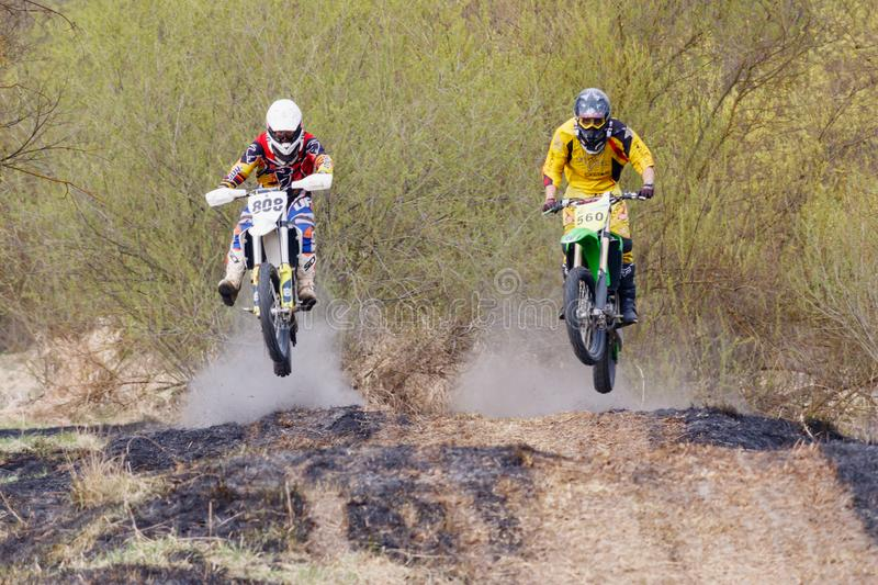 Moscow, Russia - April 13, 2019: Two racers on a cross-country motorcycles rushes along a dirt track. Training of motocross sports royalty free stock photo