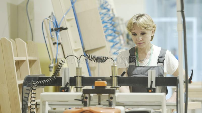 Moscow, Russia - April, 2019: Woman working on woodworking machine. Action. Woman professional focused on working with stock images