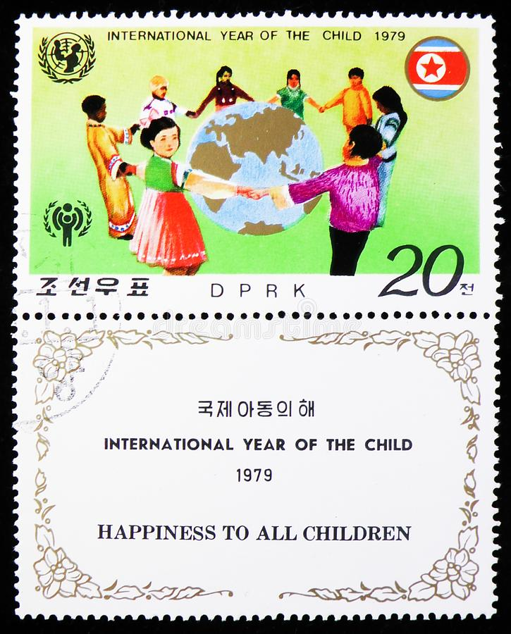 Children from different continents dancing around a globe, International year of the Child (II) serie, circa 1979. MOSCOW, RUSSIA - AUGUST 6, 2019: Postage stamp stock photography