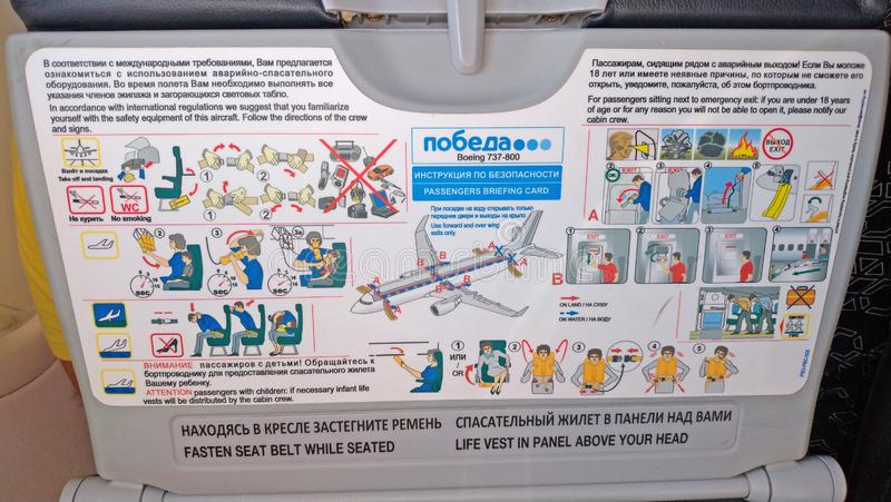 Moscow, Russia, August 5, 2018 Safety instruction aboard the Pobeda airplane. Emergency Landing and Evacuation on Water sign on royalty free stock images