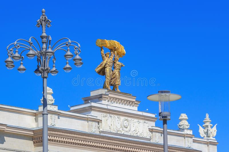 Moscow, Russia - August 01, 2018: Sculptural composition Tractor driver and collective farm girl on arch of Main entrance on VDNH. In Moscow on a blue sky stock photo