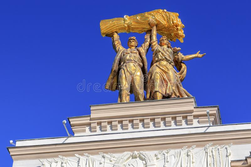 Moscow, Russia - August 01, 2018: Sculptural composition Tractor driver and collective farm girl on top of arch of Main entrance. On VDNH in Moscow against blue royalty free stock photos