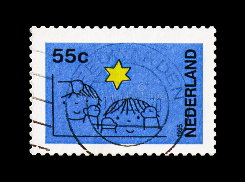 Children and star, Blue, December stamps serie, circa 1995. MOSCOW, RUSSIA - AUGUST 18, 2018: A stamp printed in Netherlands shows Children and star, Blue stock photo