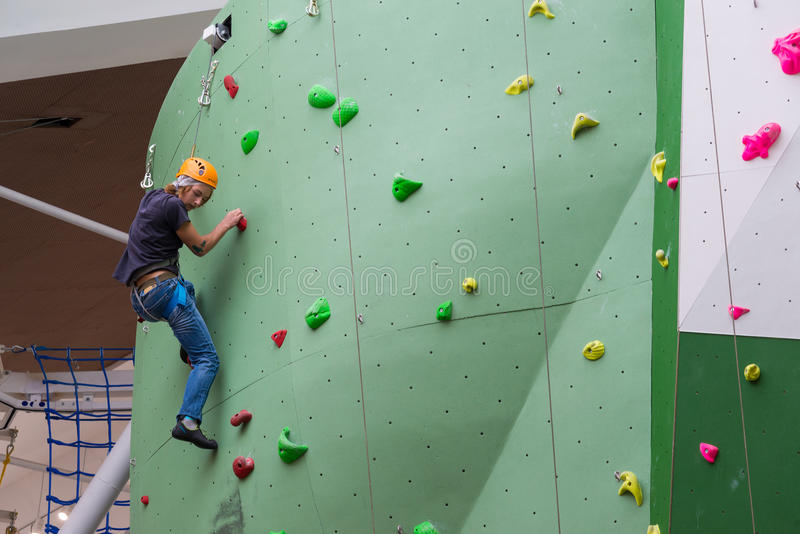 Moscow, Russia - August 30, 2016. Teen on climbing wall in shopping complex Zelenopark stock photography