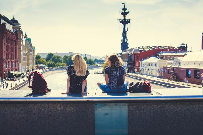 Two young girls sitting on a bridge over the Moscow river with a view to Peter the Great, Krasny Oktyabr and Muzeon park royalty free stock photo