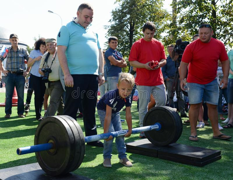 An unknown boy is trying to lift a bar at a sports festival. MOSCOW, RUSSIA - AUGUST 22, 2015:An unknown boy is trying to lift a bar at a sports festival royalty free stock photography
