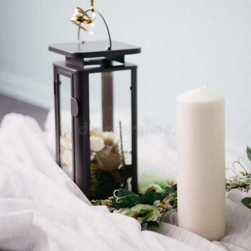 Moscow, Russia - 06 10 2018: black metal lamp with white roses, candle and flowers on light background, home decor stock image