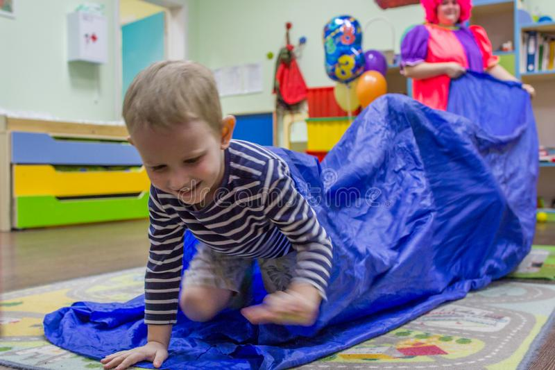 A boy getting out of the blue cloth tube. children`s competitions in kindergarten. royalty free stock images