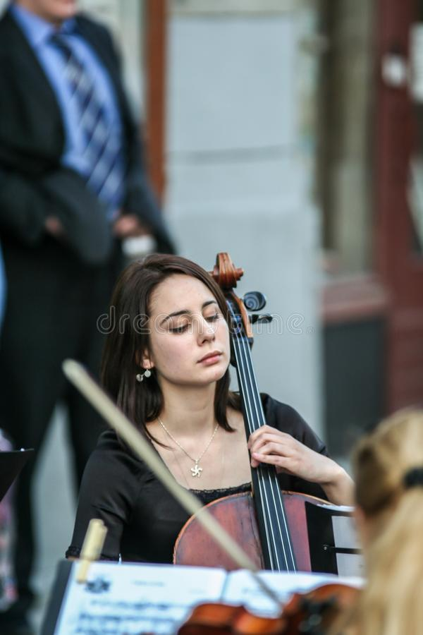 Cellist woman playing on the street, side view. stock photos