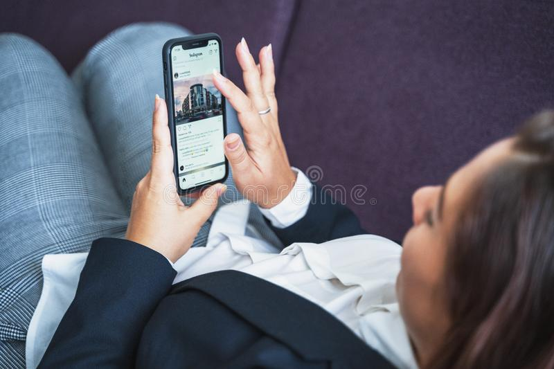 Moscow, Russia - Circa August 2019 : Young woman using Iphone and app Instagram, scrolling feed on touchscreen with. Finger, social media royalty free stock photos