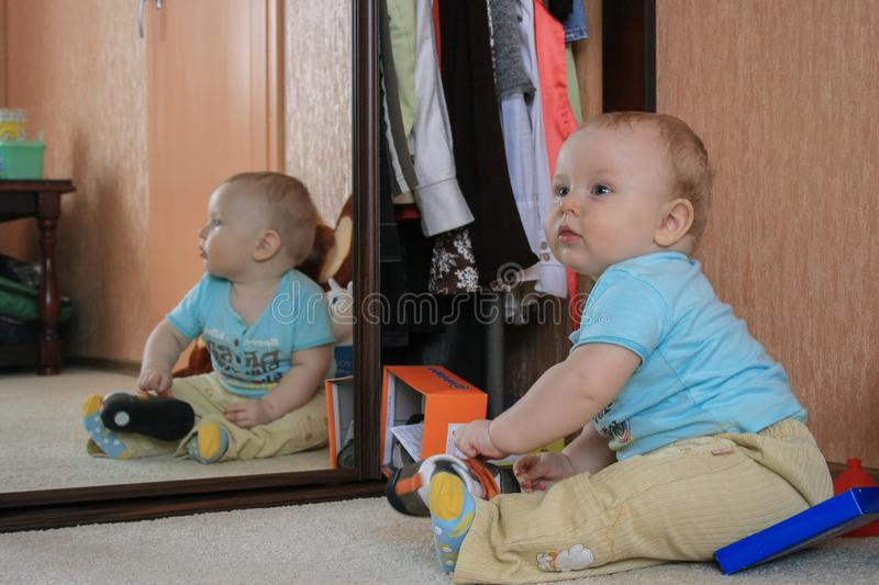 Cute baby boy sitting on the floor and playing shoes by the mirror. stock photos
