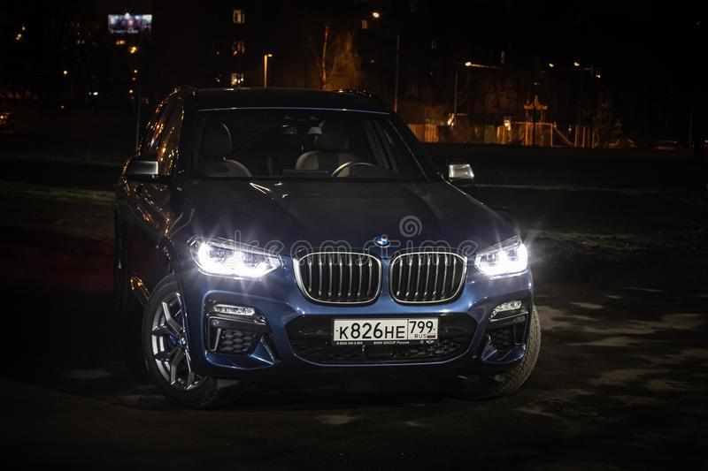 Moscow. Russia - December 06, 2019: The all-new BMW X3. Blue crossover stands on the street at night. Premium German SUV front. View royalty free stock image