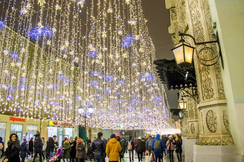 MOSCOW, RUSSIA - DECEMBER 21, 2017: People and tourists walk along street decorated for New Year and Christmas. Holidays near Kremlin. Festival Christmas light stock photography