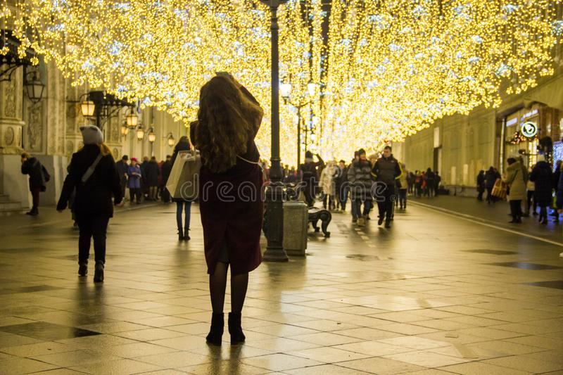 MOSCOW, RUSSIA - DECEMBER 21, 2017: People and tourists walk along street decorated for New Year and Christmas. Holidays near Kremlin. Festival Christmas light royalty free stock images