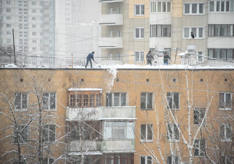 Uniformed workers dump snow from the roof. Moscow, Russia - December 6, 2018. Uniformed workers dump snow from the roof. The crow is watching carefully stock photo