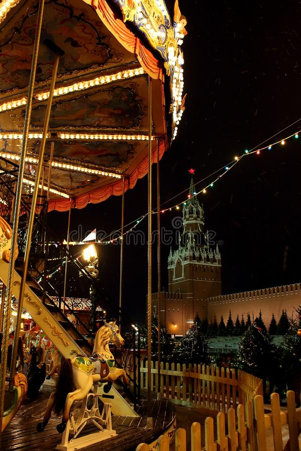 Vintage carousel on Red Square against the background of Spasskaya tower of the Kremlin during the Christmas and New year Fairs in. MOSCOW, RUSSIA - DECEMBER 8 stock photography