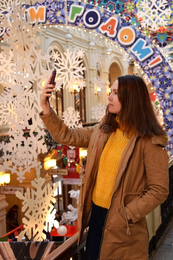 Moscow, Russia - December 16, 2018: Young woman is taking selfies in the Moscow State Department Store GUM. Decorated for New Year and Christmas stock images