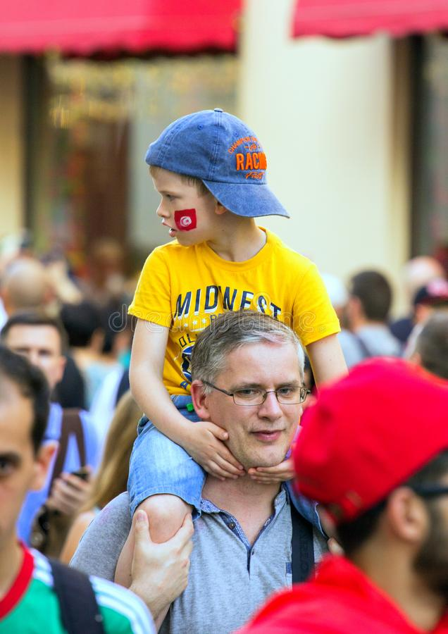Fans of football on the Moscow street. World cup 2018. Cute boy sitting on the father`s shoulders. 2018.06.23, Moscow, Russia. Fans of football on the Moscow stock photography