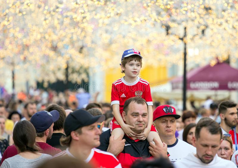 Fans of football on the Moscow street. World cup 2018. Cute boy sitting on the father`s shoulders. 2018.06.23, Moscow, Russia. Fans of football on the Moscow royalty free stock photo