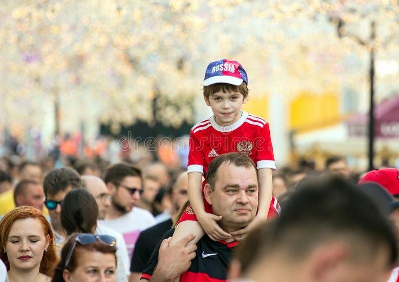 Fans of football on the Moscow street. World cup 2018. Cute boy sitting on the father`s shoulders. 2018.06.23, Moscow, Russia. Fans of football on the Moscow stock photos