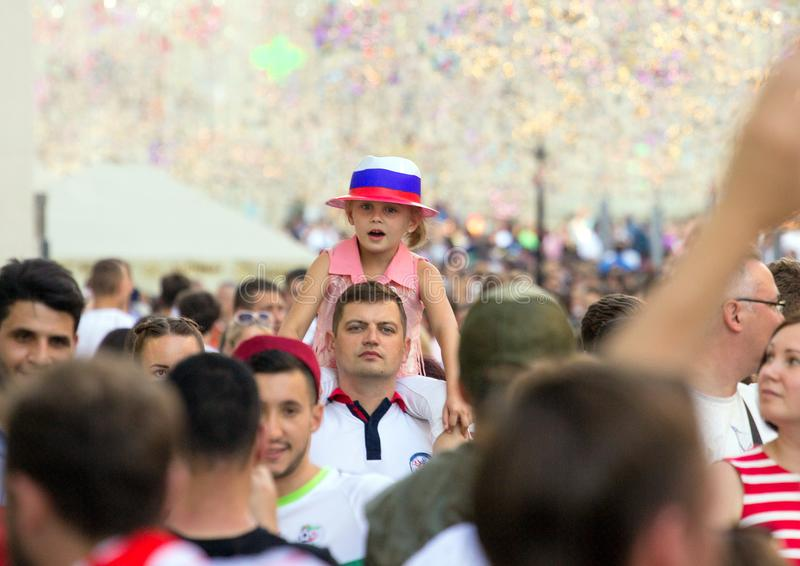 Fans of football on the Moscow street. World cup 2018. Cute girl wearing colorful hat and sitting on father`s shoulders. 2018.06.23, Moscow, Russia. Fans of royalty free stock image