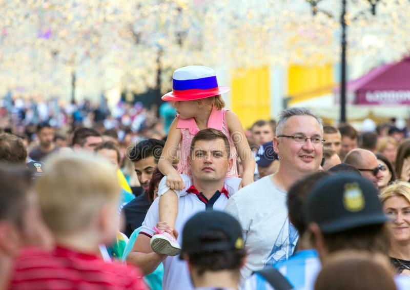 Fans of football on the Moscow street. World cup 2018. Cute girl wearing colorful hat and sitting on father`s shoulders. 2018.06.23, Moscow, Russia. Fans of royalty free stock photo