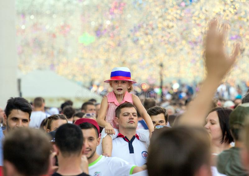 Fans of football on the Moscow street. World cup 2018. Cute girl wearing colorful hat and sitting on father`s shoulders. 2018.06.23, Moscow, Russia. Fans of royalty free stock images
