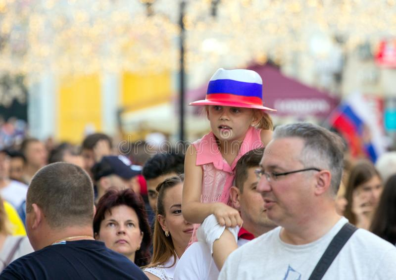 Fans of football on the Moscow street. World cup 2018. Cute girl wearing colorful hat and sitting on father`s shoulders. 2018.06.23, Moscow, Russia. Fans of stock photos