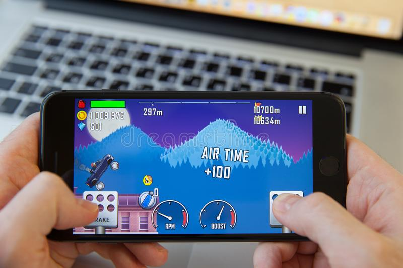 Moscow / Russia - February 20, 2019: holding an iPhone on MacBook background. hill climb racing is loading. royalty free stock image