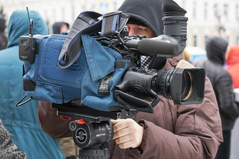 Cameraman with his camera packed in case on the Nemtsov memory march in Moscow. Moscow, Russia - February 24, 2019. Nemtsov memorial march. Cameraman with his stock photography