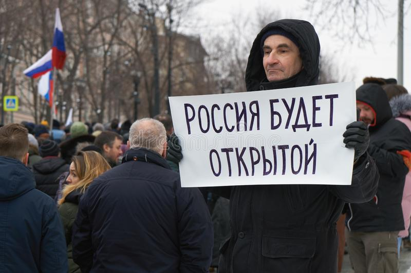 Man holding a hand written poster with words: Russia will be free on Nemtsov memory march in Moscow royalty free stock photos