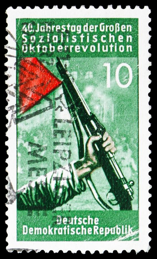 Gun and red flag, 40th anniversary of October revolution serie, circa 1957. MOSCOW, RUSSIA - FEBRUARY 22, 2019: A stamp printed in Germany, Republic shows Gun royalty free stock image