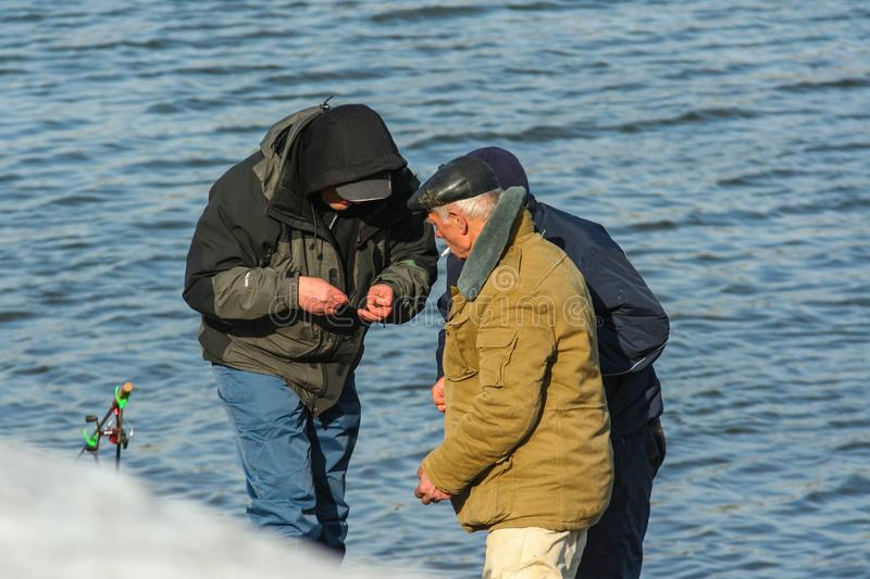 Fishermen on the river bank. Spring entertainment of Russian people. 2010.03.27, Moscow, Russia. Fishermen on the river bank. Spring entertainment of Russian stock image