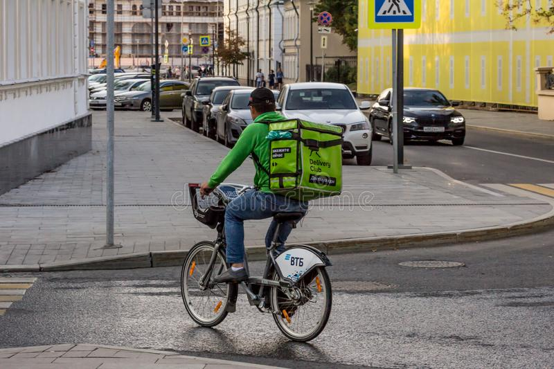 Food delivery by bike. Deliveryman cycling by road, back side view. 2019.09.07, Moscow, Russia. Food delivery by bike. Deliveryman cycling by road, back side royalty free stock images