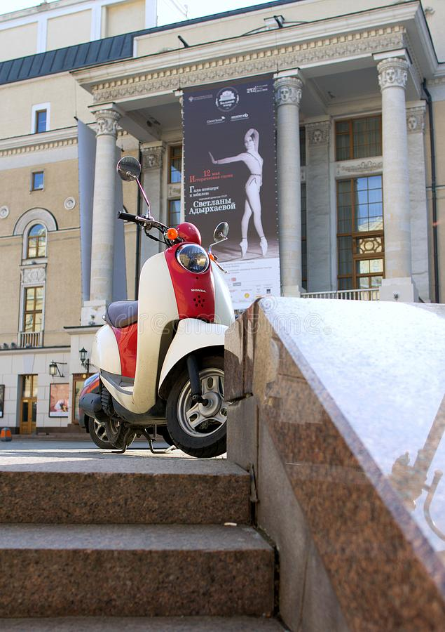 Honda`s vintage scooter on background the building of new scene of Bolshoi theatre. Moscow cityscape with transport. 2018.05.01, Moscow, Russia. Honda`s vintage stock photography