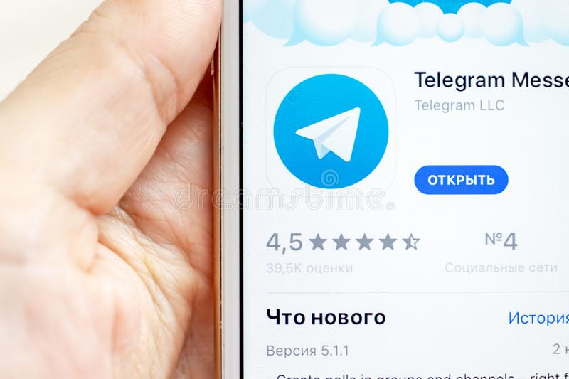 MOSCOW, RUSSIA - JANUARY 08, 2018: Hand holding Apple Iphone 7s with Telegram application downloading from app store on the screen stock photo
