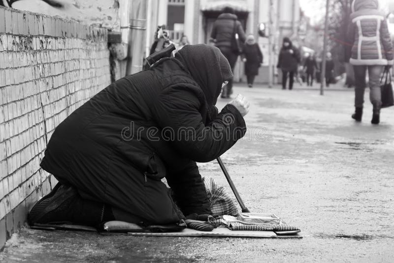 Moscow.Russia.-January 2018.Sad homeless woman sitting on the street people passing by. Black-and-white photo. royalty free stock photography