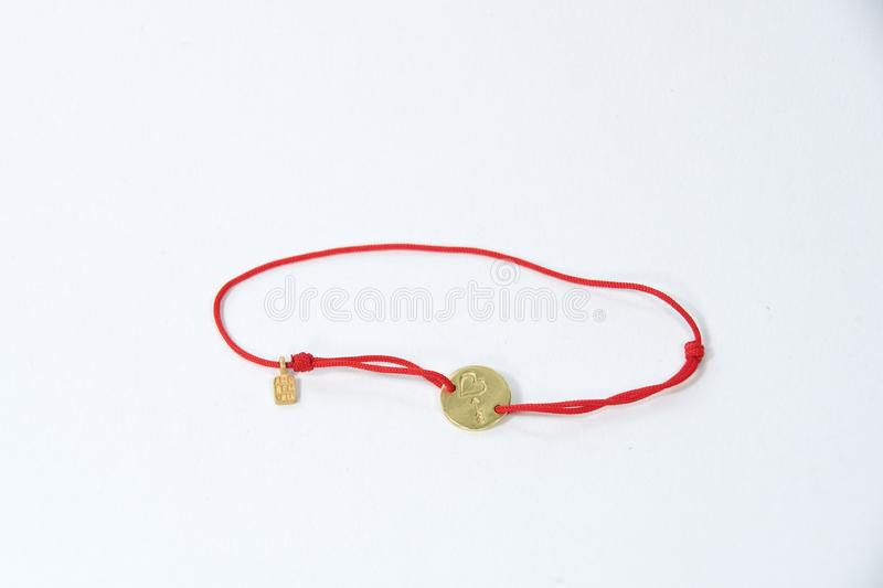 Bracelet decoration - a thread of red color on which a small plate of yellow metal stock image