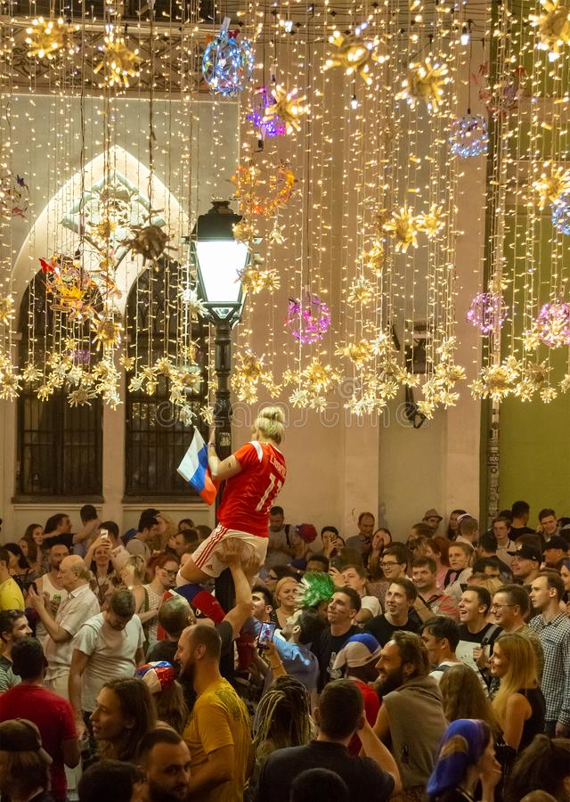 Woman is climbing on the street lamp. Football fans of different countries celebrate the victory of the Russian team over Spain royalty free stock photography