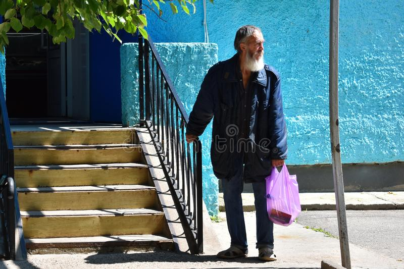 Poor homless jobless old man costs at an entrance to shop royalty free stock images