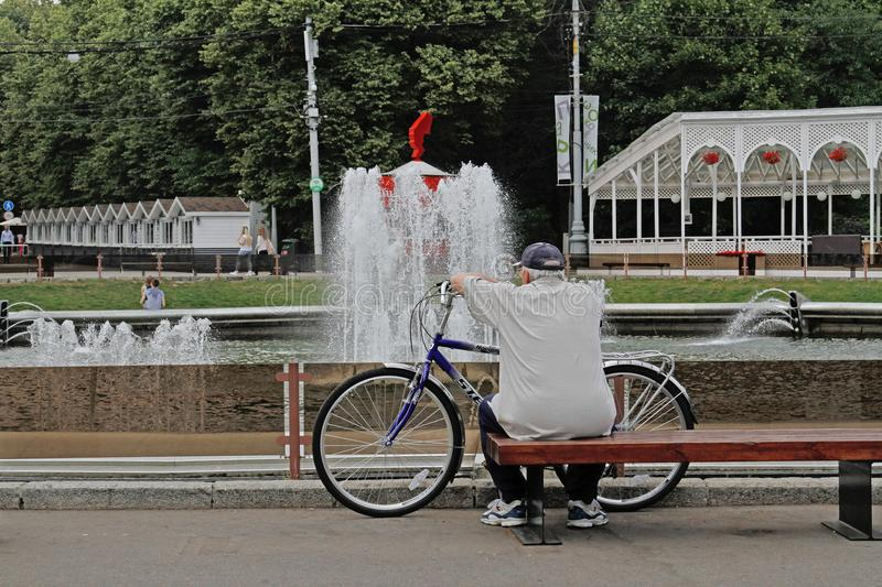 An elderly man with a bicycle sitting on a bench and looking at the fountain in the Sokolniki Park royalty free stock photography