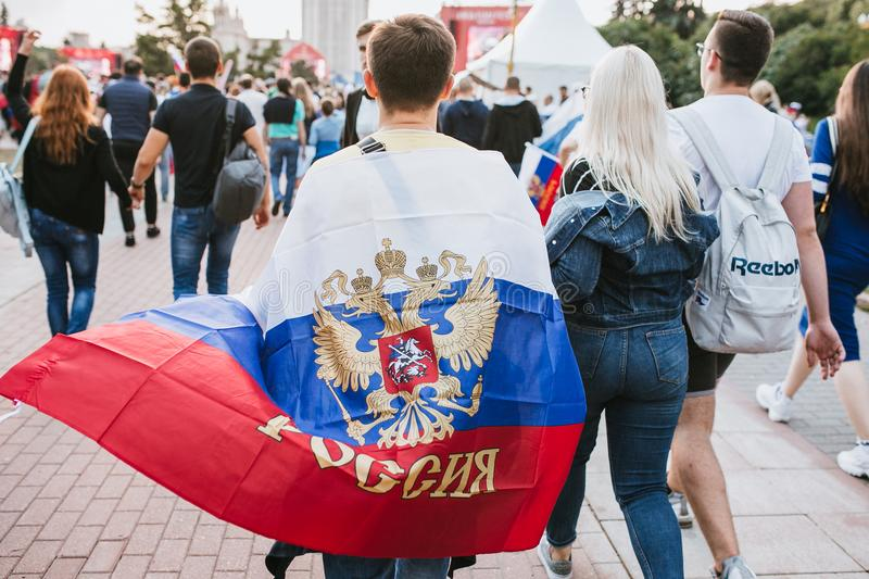 MOSCOW, RUSSIA - JULY 2018: A football fan with the flag of Russia on his shoulders on the fan zone during the World Cup. MOSCOW, RUSSIA - JULY 2018 A football stock image