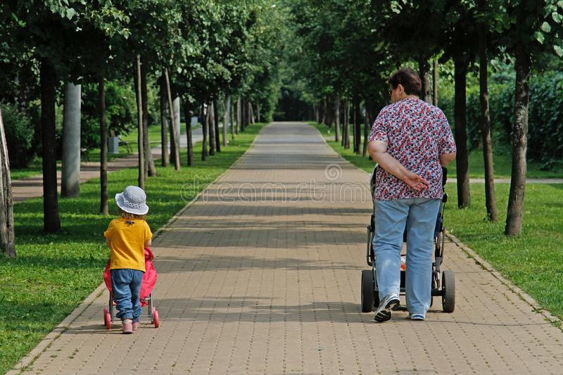Grandmother and granddaughter walking with strollers in the Park Sokolniki royalty free stock photos