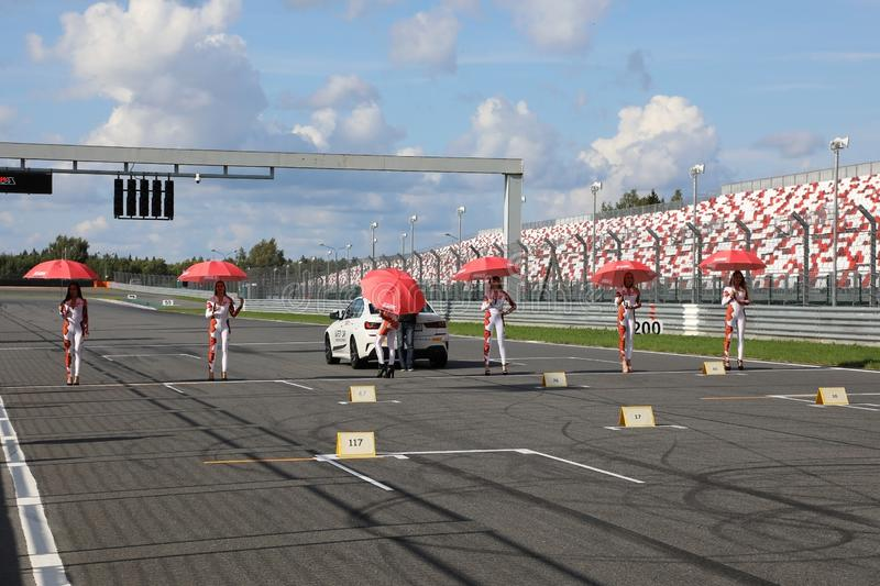 Grid girls with parasols standing on the start line royalty free stock photo