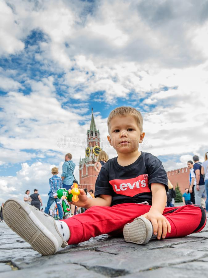 Moscow, Russia - July 7, 2018: little boy sits on Red Square paving stones, background from Spassky Tower, blue sky royalty free stock photos