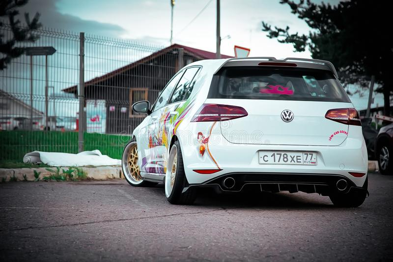 Moscow, Russia: July 06, 2019: Moscow, Russia: July 06, 2019: Bright white lowered volkswagen golf mk7 with aerography parked on stock image