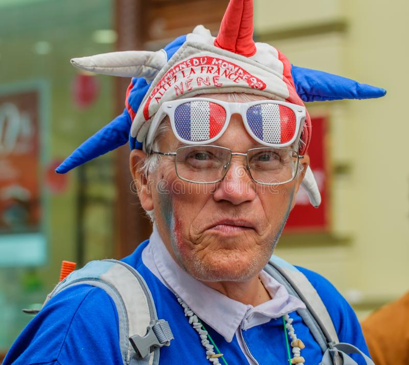 Moscow, Russia - July 7, 2018: Portrait of elderly French fan with football attribute in blue-white-red tricolor, flag stock photo